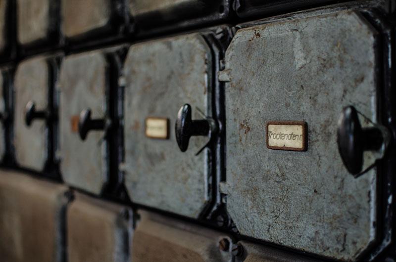 Papierschildchen, handbeschriftet an Elektrokästen